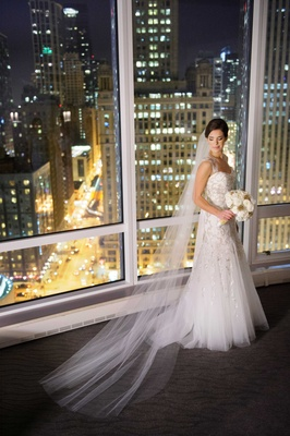 Bride in Monique Lhuillier wedding dress in front of Chicago skyline at hotel
