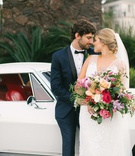 Bride with pretty braided hairstyle groom bow tie tropical bouquet rose orchid greenery classic car