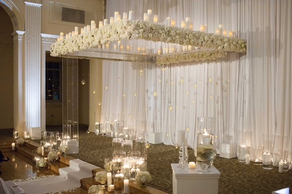 Clear ceremony structure with white flowers and candles, white aisle runner, candles on floor