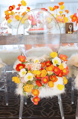 Bride seat at bridal shower ghost chair with white faux fur and lots of white yellow orange poppies