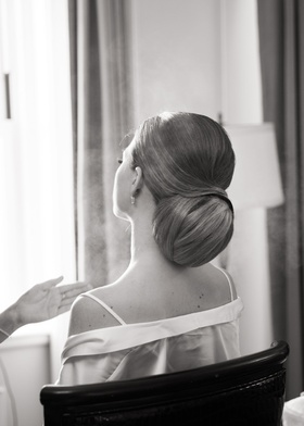 black and white photo of bride getting ready wedding in robe off shoulder with updo coiffure elegant