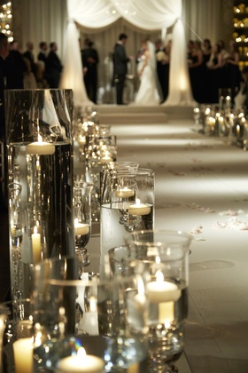 Cylindrical vases filled with water along ceremony aisle