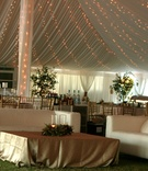 White couches and gold table under ivory tent with twinkle lights