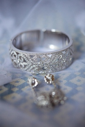 Diamond cuff bracelet and earrings on top of veil