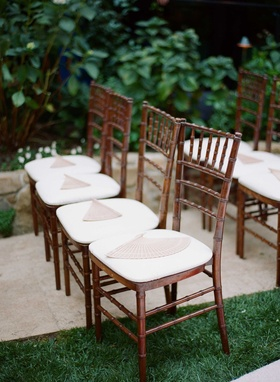 Wedding chairs on Hotel Bel-Air Swan Lake lawn with wood fans