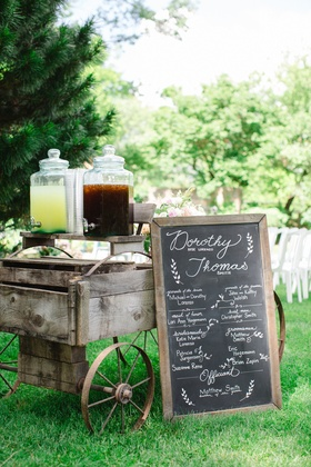 drink station on old-fashioned wooden cart and chalkboard sign lemonade iced tea