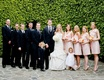 Bride and groom in front of hedge with bridesmaids and groomsmen