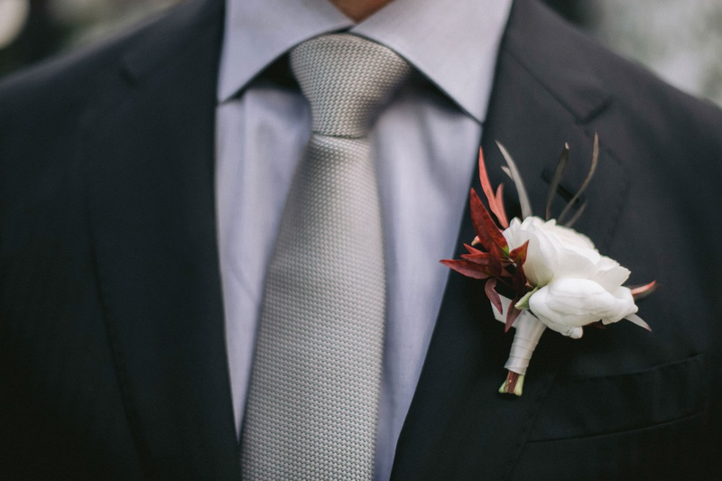 groom boutonniere white ranunculus with fall leaves foliage lilla bello