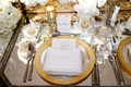 Gold rim charger plate with sparkly napkin menu tucked in mirror table with white ranunculus flowers