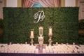 Green hedge wall with monogram behind escort card table draped with purple tablecloth