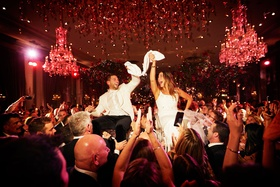 wedding reception bride and groom on chairs with guests at reception chandelier red lighting