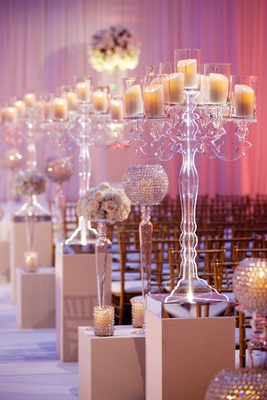 Clear Lucite candelabra with pillar candles and crystal candle votives on risers at ceremony