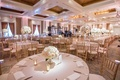 large indoor reception space round and long tables white pink tall small floral dance floor