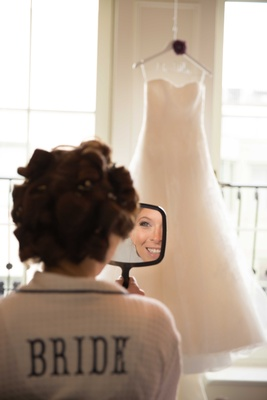 Bride with hair in curlers looking in handheld mirror in white robe embroidered with bride vera wang