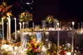 Dark wedding reception space tall candles flowers in clear boxes translucent ghost chairs