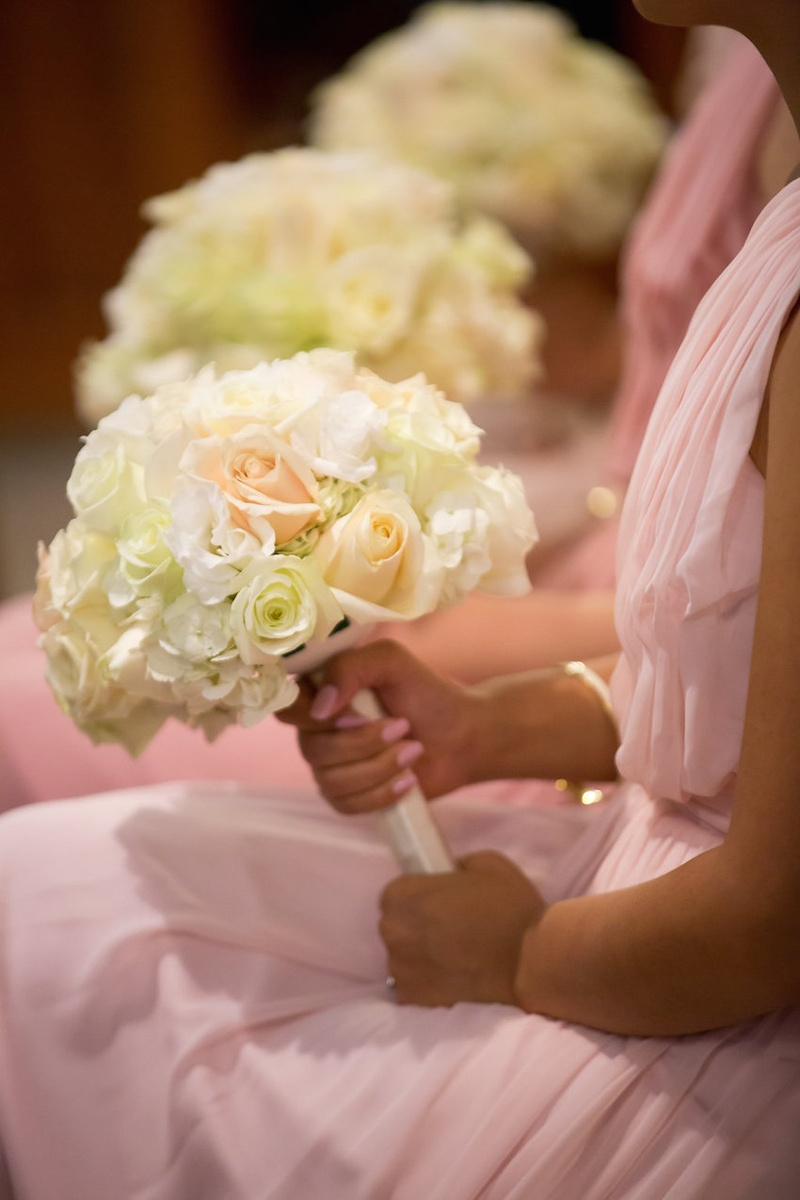 Bridesmaids in pale pink dresses hold bouquets of white hydrangreas, roses, lisianthus, peach roses