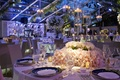 Tent wedding reception table with floating candles and white centerpiece