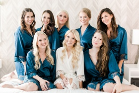 bride in white lace trim robe long blonde hair bridesmaids on bed in blue robe lace trip curled hair