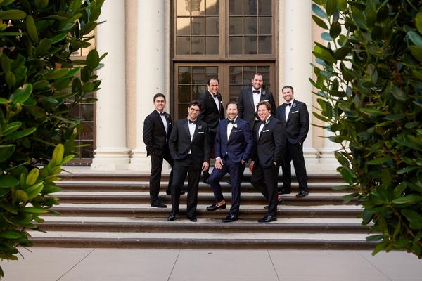 groom in navy tuxedo, groomsmen in black tuxedo