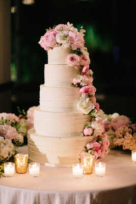 Tall white wedding cake five layers with fresh flower decorations peony garden rose white pink