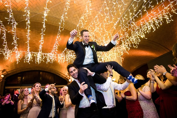 Groomsmen guests lifting groom during hora jewish wedding reception twinkle lights hanging ceiling