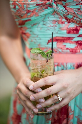 Wedding guest in summer dress holding mojito