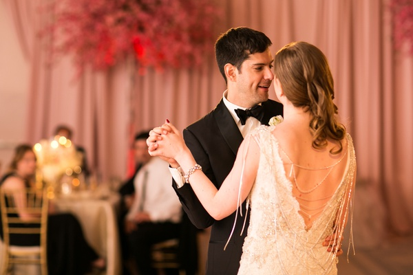 bride in 1920s inspired weddign dress by lazaro reception dress, groom in tuxedo