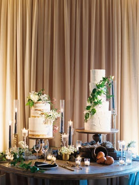 Wedding naked cake and four layer white cake with fresh greenery candles on table