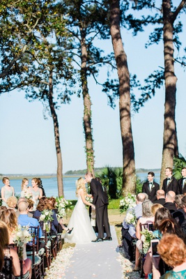 bride and groom kiss during outdoor wedding ceremony montage palmetto bluff water view flower petals