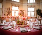 Wedding reception table with pink tablecloth lantern centerpiece with green hydrangeas and pink rose