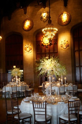 Wedding reception tables with white tablecloths, flowers, and candles
