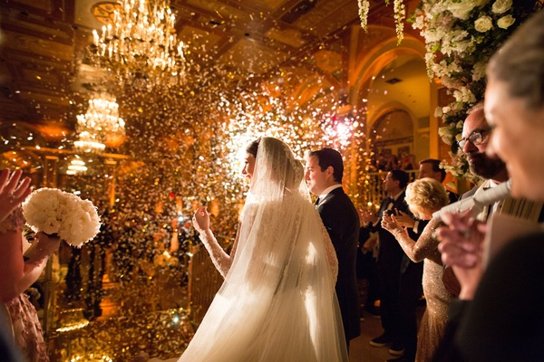 Bride and groom looking out to audience guests at wedding ceremony confetti and lights shining