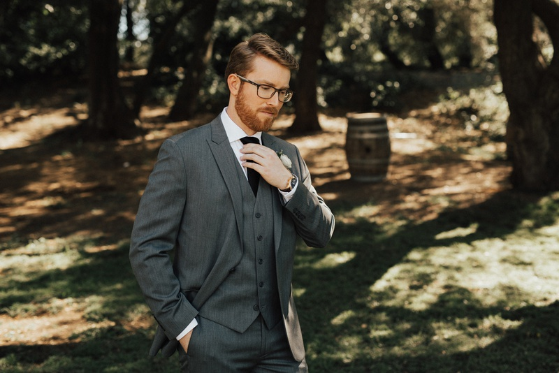 groom with glasses and beard in three-piece grey suit adjusting his black tie
