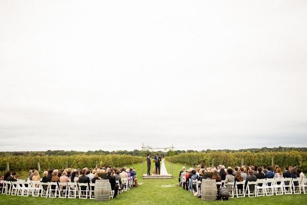 Green vineyard wedding ceremony vines white chairs chuppah jewish ceremony