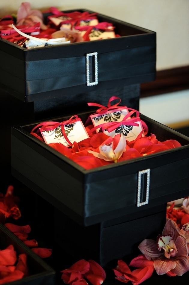 Black box filled with petals and seating cards