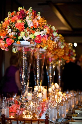 Transparent vases topped with orange flowers