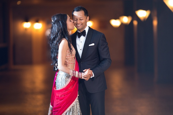 Indian bride in sari with gold top, silver skirt, and fuchsia wrap kisses groom in black tuxedo