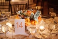 Table 14 in orange on round reception table with orange rose and dusty miller curly willow branch
