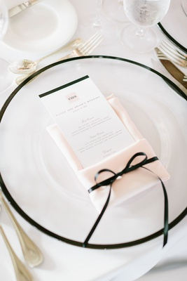 clear charger plate, blush napkin with menu tied on with thin black ribbon