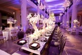 Purple wedding reception with long formal table in center