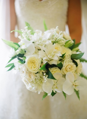 Bride holding bouquet of white garden roses, orchids, lilies, lily of the valley, and greenery