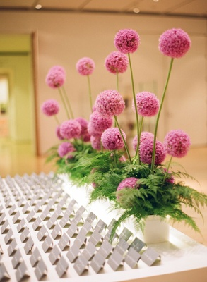 pink allium flowers in planter with ferns in front at modern museum escort card table