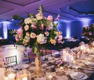 large floral centerpieces with candles, blue violet uplighting