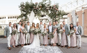 bride and groom on bridge ceremony with bohemian vintage bridesmaid dresses grey groomsmen jackets