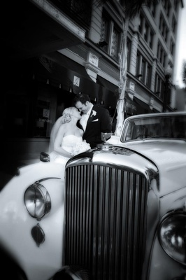 Black and white photo of couple kissing by car