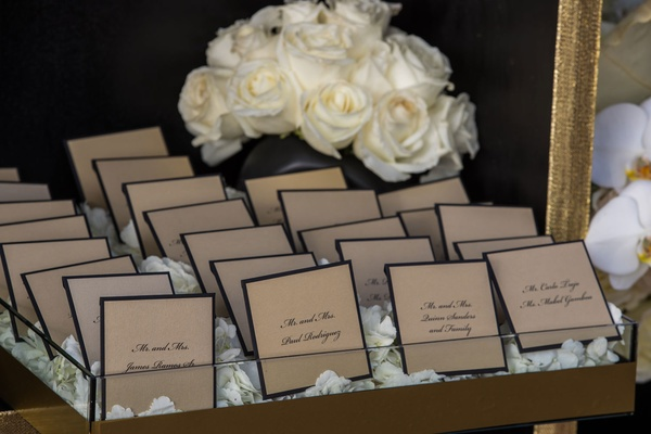 Wedding reception escort cards trays with white rose petals gold and black border seating cards rose