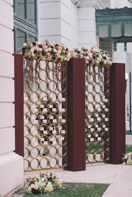 burgundy pillars with glass pane gold rings escort cards, florals on top