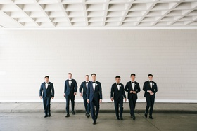 groom and groomsmen walking toward camera with bow ties and boutonnieres