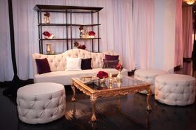 Vibiana wedding lounge area with tufted ottoman, sofa, and gold coffee table