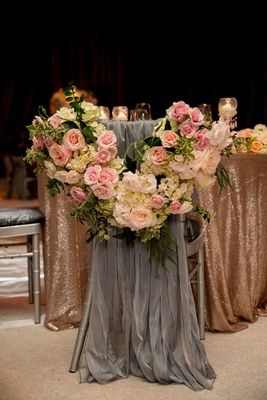 Grey fabric draped over bride's chair with flower garland at gold sequin sweetheart table